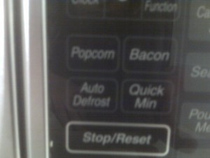 control panel of a microwave with a button for popcorn and a button for bacon
